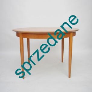 Drewniany stół o modernistycznej formie lat 50/60. Rozkładany prostym i funkcjonalnym systemem motylkowym.Drewno z rodziny mahoniowych barwione na jasny tek (nogi i obłóg blatu). Blat fornirowany tekiem/orzechem.