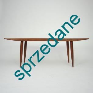 Modernistyczna, ciekawa forma. Efektowny minimalizm. Piękne wybarwienie i rysunek usłojenia. Nogi i obrzeża z masywu tekowego. Blat fornirowany tekiem. Nogi odkręcane. Drewno olejowane. Oryginalny produkt duński lat 60-tych.