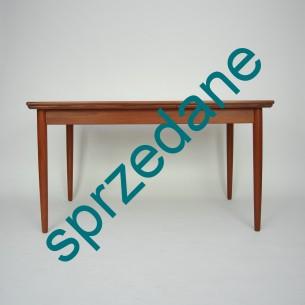 Tekowy stół rozkładany. Modernistyczna forma lat 60-tych. Nogi i obrzeża z litego teku. Reszta fornirowana. Piękne usłojenie kontynuowane na wszystkich blatach. Mebel olejowany. Dwie kombinacje rozłożenia. Produkt duński z sygnaturą najwyższej jakości.