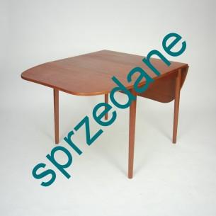 Niezwykle funkcjonalny mebel. Pięć kombinacji rozłożenia. Dwa blaty wiszące i dwa dokładane. Od malutkiego stolika do okazałego stołu. Ładne wcięcie na krótszym boku blatu. Lite drewno tekowe i fornir olejowane. Produkt duński lat 60 – tych.