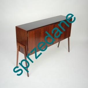 Subtelna komódka z wytwórni OMAN JUN. Drewno i fornir palisandrowy. Górny blat lakierowany. Produkt duński lat 60/70.