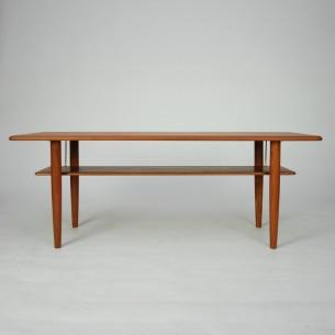 Modernistyczny, duński stolik. Zgrabna forma z praktyczną półką. Blaty fornirowane, nogi i półka z masywu teku. Mocowania dolnego blatu mosiężne. Produkt duński lat 60-tych.
