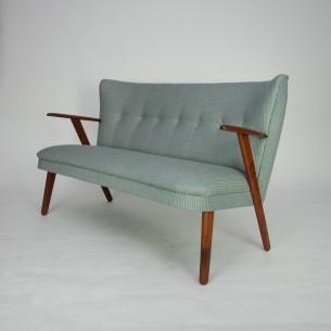 Duńska klasyka lat 50-tych. Lekka i efektowna forma. Konstrukcja drewniana. Podłokietniki i nogi tekowe (olejowane). Hiszpańska, wysokogatunkowa tkanina (60 % poliester 40% wełna). Siedzisko na sprężynach.