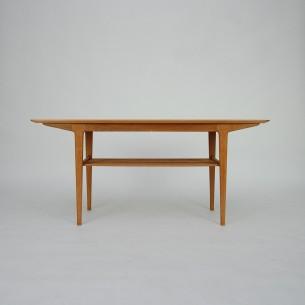 Modernistyczny, duński stolik. Zgrabna forma z ażurową półką. Blat fornirowany, nogi i półka z dębu. Całość drewniana. Mebel olejowany. Produkt duński lat 60-tych. Manufaktura JANSON RINGSTED.