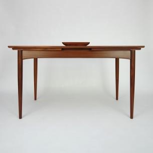 Tekowy stół rozkładany. Modernistyczna forma lat 60-tych. Nogi i obrzeża z litego teku. Reszta fornirowana. Piękne usłojenie kontynuowane na wszystkich blatach. Mebel olejowany. Dwie kombinacje rozłożenia. Produkt duński.