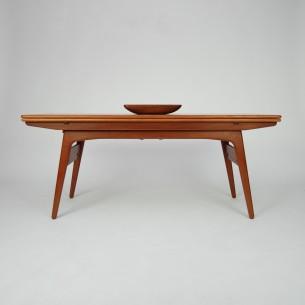 Duński stolik z funkcją stołu. Stolik kawowy zmienia się w prosty sposób w stół o typowej wysokości. Nogi, rama i obrzeża blatu z litego teku. Blat fornirowany naturalnym tekiem. Drewno olejowane. Produkt duński lat 60-tych.
