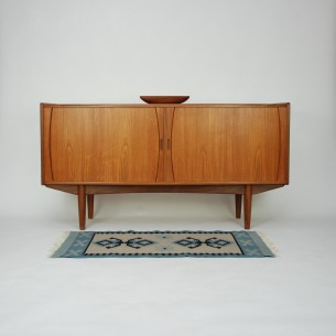 Wyjątkowa duńska komoda. Zgrabna minimalistyczna forma. Efektowne, misternie wykonane drzwiczki roletowe. Fornir tekowy. Obrzeża skrzyni, ciągadła i nogi z litego teku. Drewno olejowane. Unikatowy produkt lat 60-tych.
