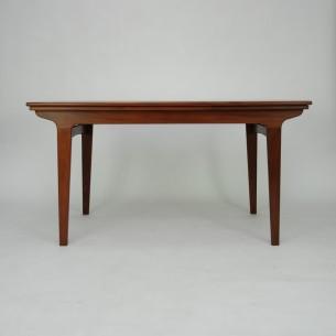 Tekowy stół rozkładany. Modernistyczna forma lat 60-tych. Nogi i obrzeża z litego teku. Reszta fornirowana naturalnym tekiem. Boki blatów w kształcie łuków. Mebel olejowany. Dwie kombinacje rozłożenia. Produkt duński.