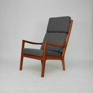 Modernistyczny, tekowy fotel projektu Ole Wanscher'a. Piękna minimalistyczna forma. Imponująca ilość litego teku. Cała widoczna konstrukcja z teczyny. Dno na sprężynach. Poduszki na piance. Drewno olejowane. Oryginalny produkt duński lat 70-tych.