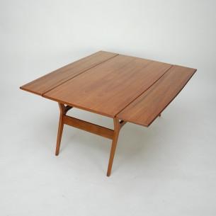Duński stolik z funkcją stołu. Stolik kawowy zmienia się w prosty sposób w stół o wysokości 67 cm. Idealne rozwiązanie dla małych mieszkań gdzie brakuje stołu.  Podnosząc blat, siedzimy na fotelach i możemy spożyć posiłek w wygodny sposób. Nogi, rama i obrzeża blatu z litego teku. Blat fornirowany naturalnym tekiem. Drewno olejowane. Produkt duński lat 60-tych.