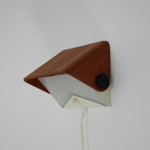 Minimalistyczny kinkiet z profilowanej sklejki fornirowanej naturalnym tekiem. Metalowy stelaż i biła plexi. Produkt duński.