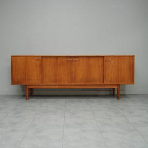 Wyjątkowy, duński sideboard. Wyrafinowana forma lat 60-tych. Efektowny minimalizm. Skrzynia fornirowana naturalnym tekiem, wykończona litą ramą. Wnętrze dębowe. Doklejki, nogi, cokół szuflady i ciągadła z masywu tekowego. Szuflady drewniane wyłożone suknem konferencyjnym. Duża szuflada z przesuwnym przybornikiem. Unikatowy system szynowy. Drzwiczki komody wiszącą. Drewno olejowane. Oryginalny produkt duński lat 60/70-tych. Pozycja unikatowa. Gratka dla fanów duńskiego modernizmu.