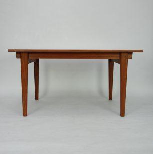 Tekowy stół rozkładany. Modernistyczna forma lat 60-tych. Nogi i obrzeża z litego teku. Reszta fornirowana naturalnym tekiem. Blat główny jest przesuwany na prowadnicach dla udostępnienia miejsca blatu dodatkowemu. Produkt duński.
