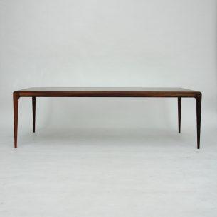 Wytworny stolik kawowy w palisandrze autorstwa Johannes'a Andersena. Blat fornirowany naturalnym palisandrem. Nogi z litego palisandru. Drewno olejowane.  Mebel sygnowany CFC Silkeborg. Oryginalny produkt duński lat 60-tych.