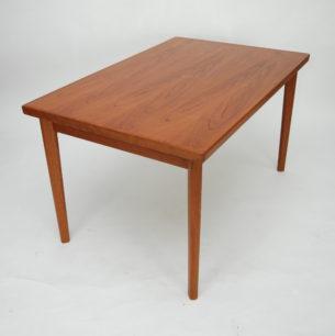 Tekowy stół rozkładany. Modernistyczna forma lat 60-tych. Projekt Henning Kjaernulf dla AM Mobler. Nogi i obrzeża z litego teku. Reszta fornirowana naturalnym tekiem. Blat główny skrywa dodatkowe, wysuwane blaty. Produkt duński.