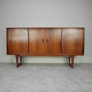 Wytworny, palisandrowy bufet. Wybitna forma lat 60/70-tych. Projekt Edmund Jørgensen. Bogate, misterne wykończenie. Absolutna dbałość o detale. Drewniane szuflady. Podświetlany barek. Drewno olejowane. Oryginalny produkt duński.