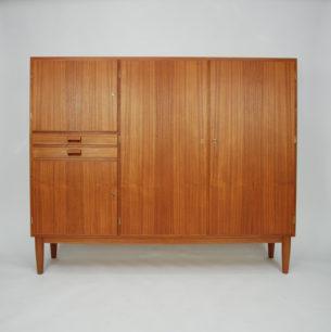 Prosta, modernistyczna forma autorstwa ikony duńskiego meblarstwa Børge Mogensen'a. Naturalny fornir tekowy. Lite, czołowe doklejki oraz pochwyty z teczyny. Drewno olejowane. Produkt duński lat 60-tych.